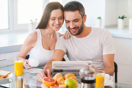 morning breakfast: Good morning starts from good news. Beautiful young couple bonding to each other and reading newspaper together while sitting in the kitchen and having breakfast