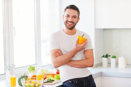 frescura: La comida sana es la vida saludable. Apuesto joven sosteniendo ají amarillo fresco y sonriente mientras está de pie en la cocina Foto de archivo