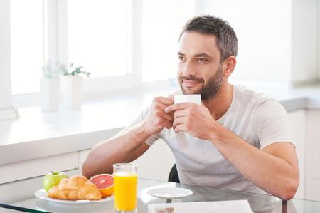 A partir journée avec un café frais et chaud. Beau jeune homme jouissant du café frais tout en étant assis dans la cuisine