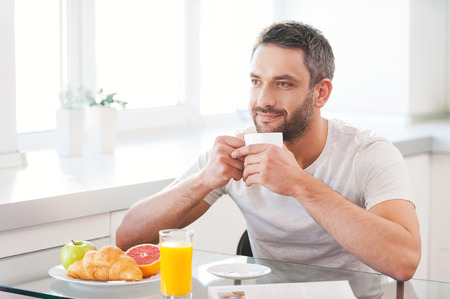 breakfast cup: Starting day with fresh and hot coffee. Handsome young man enjoying fresh coffee while sitting in the kitchen