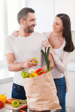 Enjoying happy and healthy life together. Beautiful young couple unpacking shopping bag full of fresh vegetables and smiling while standing in the kitchen together photo