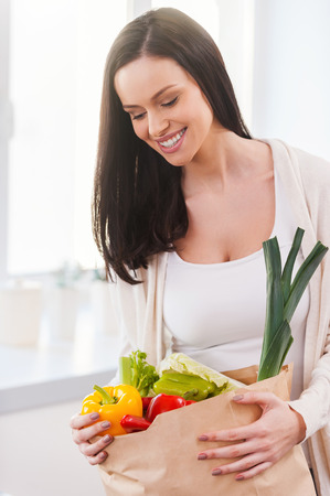 Bag full of health and colors. Beautiful young woman unpacking shopping bag full of fresh vegetables and smiling while standing in the kitchen photo
