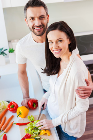 Happy and healthy couple. Top view of beautiful young couple bonding to each other and smiling while preparing food in the kitchen together photo