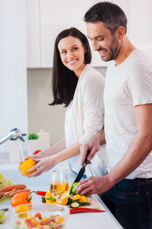 heterosexual couple: Cooking together is fun. Beautiful young loving couple cooking together while standing in the kitchen