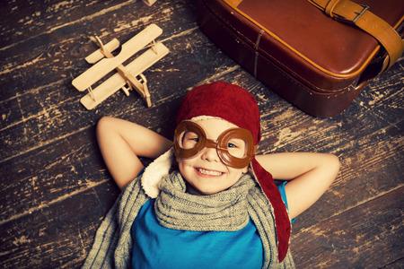 piloto: So�ando con un gran cielo. Vista superior de ni�o feliz en sombreros piloto y gafas acostado en el piso de madera y sonriendo mientras cepilladora de madera y el malet�n que se cerca de �l