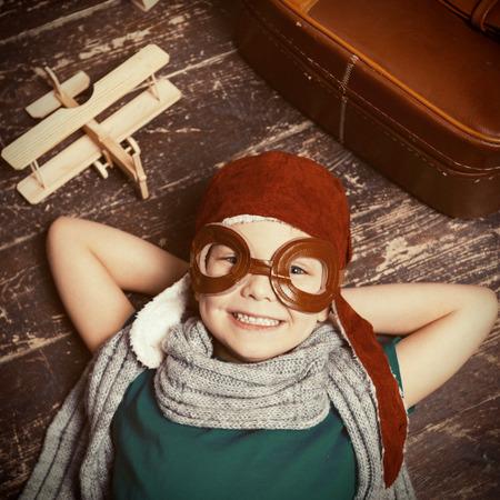 juguetes de madera: Poco vista dreamer.Top feliz de ni�o feliz en sombreros piloto y gafas acostado en el piso de madera y sonriendo mientras cepilladora de madera y el malet�n que se cerca de �l
