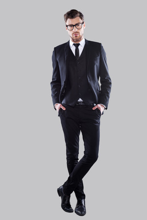 sex symbol: Perfection in every detail. Full length of confident young man in formalwear and eyeglasses holding hands in pockets and looking at camera while standing against grey background