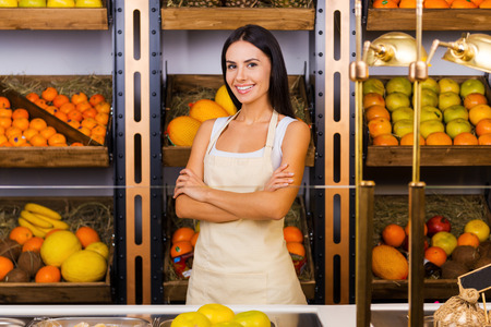 freshest: Only the freshest fruits in our store. Beautiful young woman in apron keeping arms crossed and smiling while standing in grocery store with variety of fruits in the background