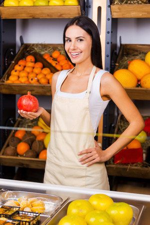 freshest: The freshest fruits in town. Beautiful young woman in apron holding pomegranate and smiling while standing in grocery store with variety of fruits in the background Stock Photo