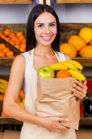 The bag full of health. Beautiful young woman in apron holding paper shopping bag with fruits and smiling while standing in grocery store with variety of fruits in the background photo