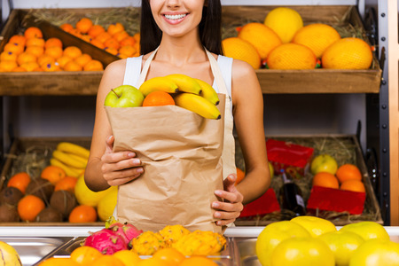 selling service smile: Selling health. Cropped image of beautiful young woman in apron holding paper shopping bag with fruits and smiling while standing in grocery store with variety of fruits in the background Stock Photo