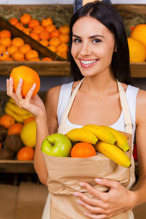 Join healthy lifestyle. Beautiful young woman in apron holding paper shopping bag with fruits and smiling while standing in grocery store with variety of fruits in the background photo