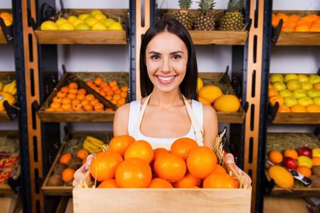 naranja fruta: Las mandarinas frescas para usted. Joven y bella mujer en el delantal con contenedores de madera con mandarinas y sonriendo mientras est� de pie en la tienda de comestibles con variedad de frutas en el fondo