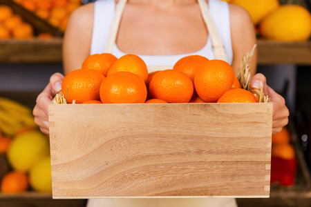 freshest: The freshest tangerines. Cropped image of young woman in apron holding wooden container with tangerines while standing in grocery store with variety of fruits in the background