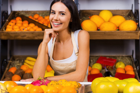 selling service smile: I love my job! Beautiful young woman in apron holding hand on chin and smiling while standing in grocery store with variety of fruits in the background