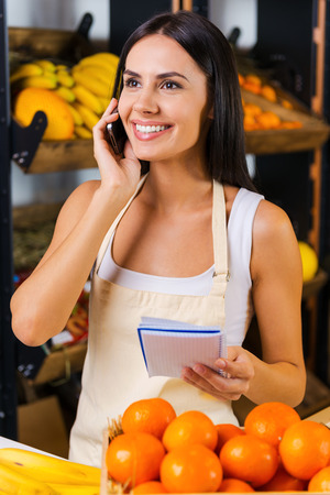selling service smile: Taking order on fruits. Cheerful young woman in apron talking on mobile phone and holding note pad while standing in grocery store with variety of fruits in the background