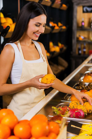 selling service smile: Working in fruit paradise. Beautiful young woman in apron working in grocery store with variety of fruits in the background Stock Photo
