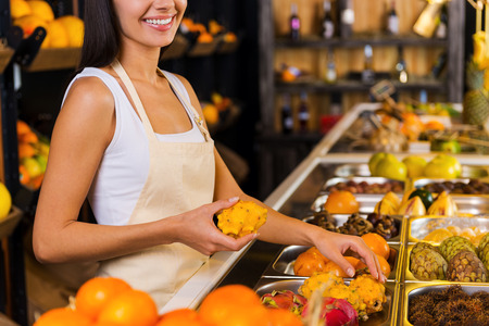 freshest: Choosing the freshest fruits for you. Cropped image of beautiful young woman in apron working in grocery store with variety of fruits in the background Stock Photo