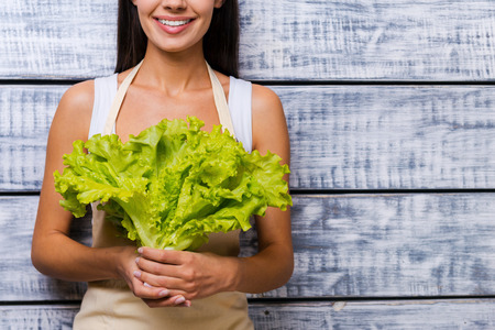 freshest: The freshest lettuce for you. Cropped image of beautiful young woman in apron holding fresh lettuce and smiling while standing in front of wooden background
