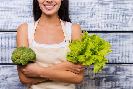 personas de pie: Verde y saludable comida. Recorta la imagen de una hermosa joven sonriente en el delantal de la celebración de la lechuga fresca y brócoli mientras está de pie delante de fondo de madera Foto de archivo