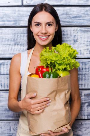 mandil: Salud en sus manos. Joven y bella mujer en el delantal de la celebraci�n de bolsa de papel llena de verduras frescas y sonriendo mientras est� de pie delante de fondo de madera