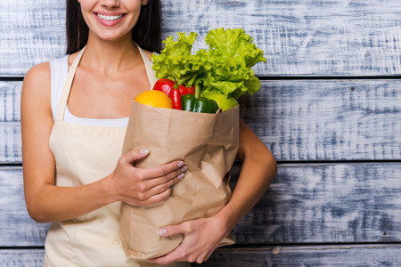 Carrying a healthy bag. Cropped image of beautiful young woman in apron holding paper shopping bag full of fresh vegetables and smiling while standing in front of wooden background