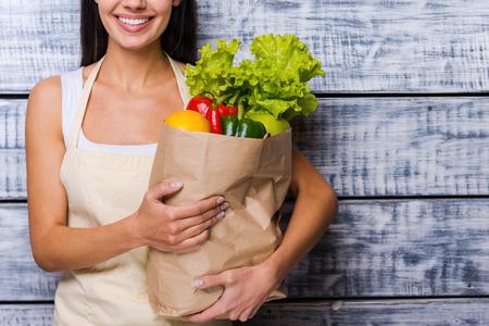 abarrotes: Llevar una bolsa sana. Recorta la imagen de mujer joven y hermosa en el delantal de la celebraci�n de bolsa de papel llena de verduras frescas y sonriendo mientras est� de pie delante de fondo de madera
