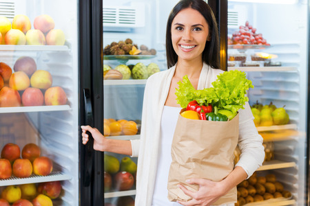freshest: Buying the freshest products. Beautiful young woman holding shopping bag with fruits and smiling while standing in grocery store near refrigerator Stock Photo