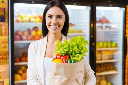 apple paper bag: Happy to find everything I want. Beautiful young woman holding shopping bag with fruits and smiling while standing in grocery store near refrigerator