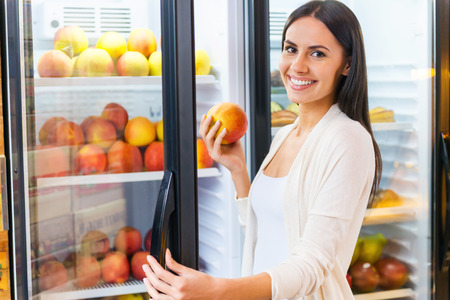 Choosing the freshest apple. Beautiful young smiling woman choosing apples from refrigerator in grocery store photo