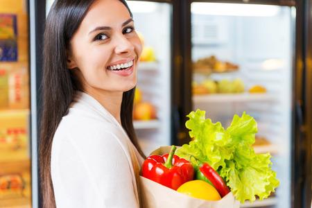 tiendas de comida: Elijo productos org�nicos. Mujer joven hermosa que sostiene el bolso de compras con las frutas y sonriendo mientras est� de pie en la tienda de comestibles cerca de frigor�fico Foto de archivo