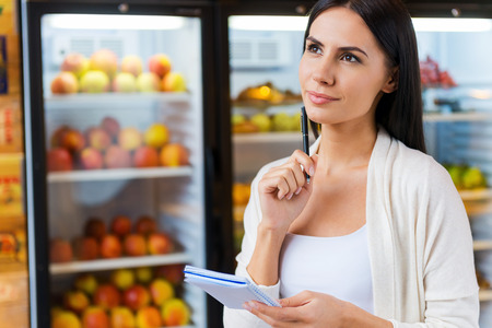 shopping list: Woman with shopping list. Thoughtful young woman holding shopping list and looking away while standing in front of refrigerators in grocery store