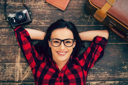 mujer con maleta: Listo para un gran viaje. Vista superior de la joven y bella mujer en gafas acostado en el piso de madera y sonriendo mientras maleta y cámara que coloca cerca de ella