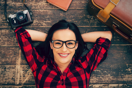 eyewear: Ready to a big trip. Top view of beautiful young woman in eyewear lying on the hardwood floor and smiling while suitcase and camera laying near her