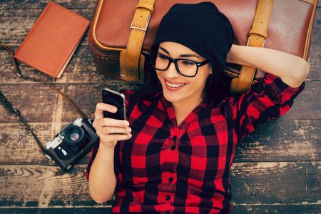 旅遊: 長途旅行後放鬆身心。美麗的年輕女子頭飾躺在地板上拿著手機和微笑俯視圖 版權商用圖片