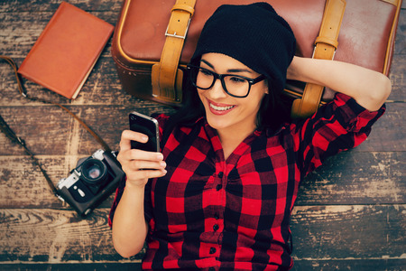 group objects: Relaxing after long trip. Top view of beautiful young woman in headwear lying on the floor holding mobile phone and smiling