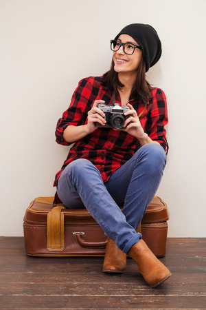 looking away from camera: Full of inspiration.  Beautiful young woman in headwear holding camera and looking away while sitting on suitcase Stock Photo