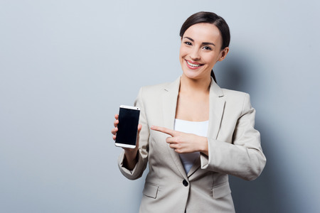 business woman phone: Your advertising on her phone. Beautiful young businesswoman holding mobile phone and pointing on it while standing against grey background