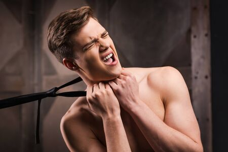 choking: Got you! Frustrated young man choking by his necktie while standing against metal background Stock Photo