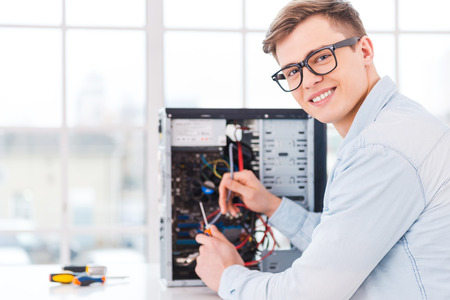 He loves his job. Portrait of handsome young man repairing computer while sitting at his working place