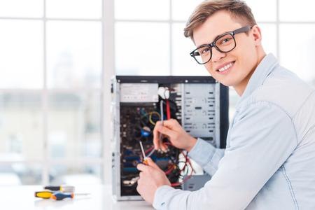trabajando en computadora: Le encanta su trabajo. Retrato de hombre joven y guapo que repara el ordenador mientras est� sentado en su lugar de trabajo Foto de archivo