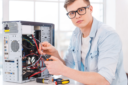Smart professional. Portrait of handsome young man repairing computer while sitting at his working place Standard-Bild