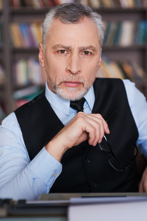 grey hair: Confident author. Confident grey hair senior man in formalwear sitting at the typewriter and looking at camera with bookshelf in the background 스톡 사진