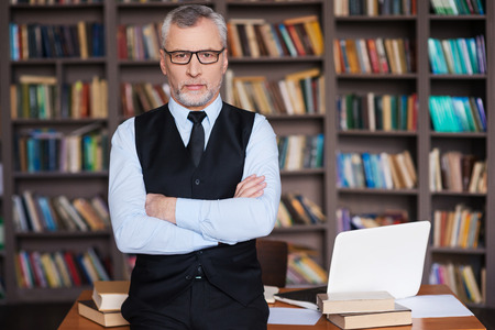 Confident professor. Confident grey hair senior man in formalwear keeping arms crossed and looking at camera while leaning at the table and with bookshelf in the background Foto de archivo