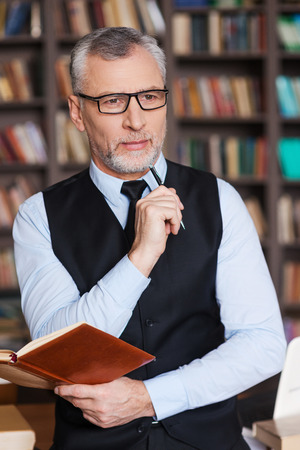 business attire teacher: Looking for inspiration. Thoughtful grey hair senior man in formalwear holding note pad and looking away while leaning at the table and with bookshelf in the background
