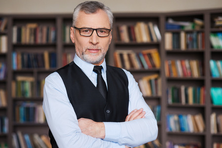 business attire teacher: Confident and intelligence. Confident grey hair senior man in formalwear keeping arms crossed and looking at camera while standing against bookshelf