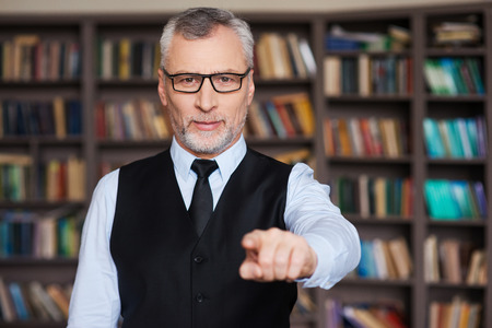 choose university: I choose you! Confident grey hair senior man in formalwear pointing you while standing against bookshelf Stock Photo