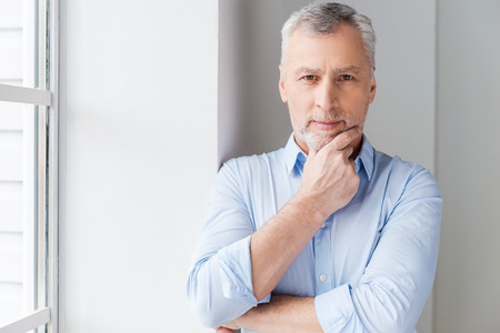 grey hair: Thinking about solutions. Thoughtful grey hair senior man in shirt looking away while standing near the window