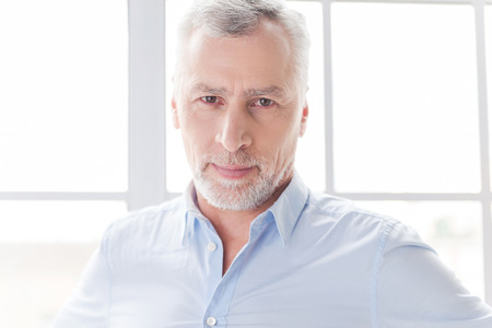 grey hair: Confident and successful. Confident grey hair senior man in shirt looking ay camera while standing in front of the window