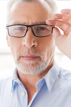 one senior man only: Confident look. Confident grey hair senior man in shirt adjusting his eyeglasses and looking at camera while standing in front of the window Stock Photo